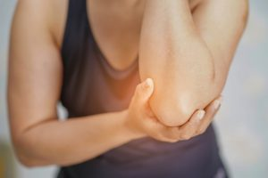 A female holding her elbow due to pain