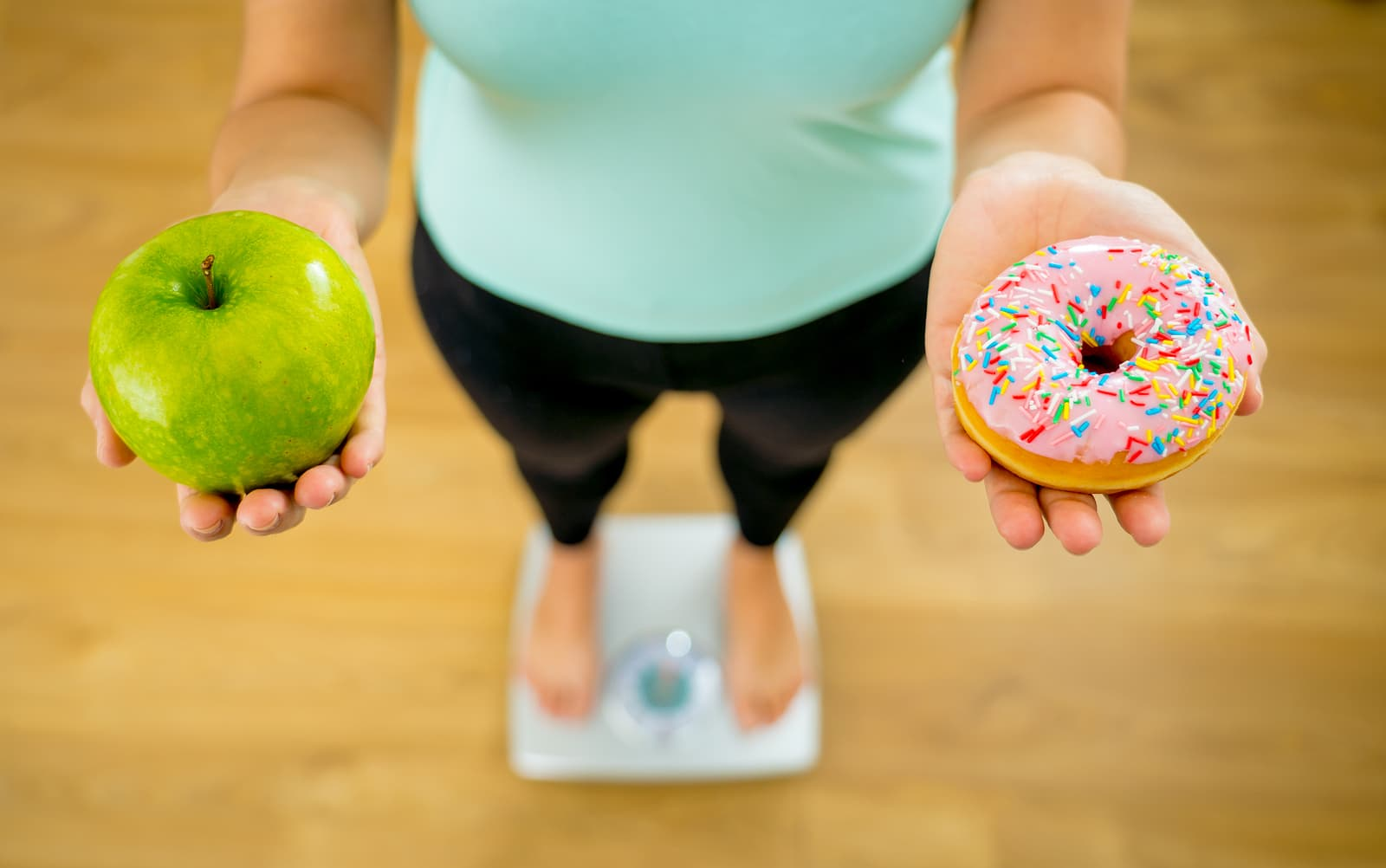 Close up of woman on scale holding fresh piece of fruit green apple and a doughnut in the other