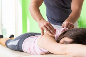 Young doctor chiropractor massaging patient
