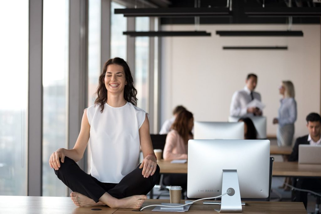 Peaceful female employee meditating at workplace in shared office