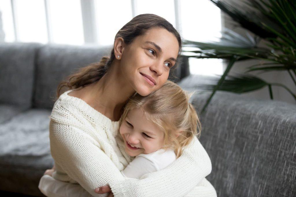 Loving mother hugging little daughter