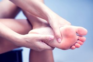 Save Download Preview Pain in the foot, girl holds her hands to her feet, foot massage, cramp, muscular spasm, red accent on the foot, close-up