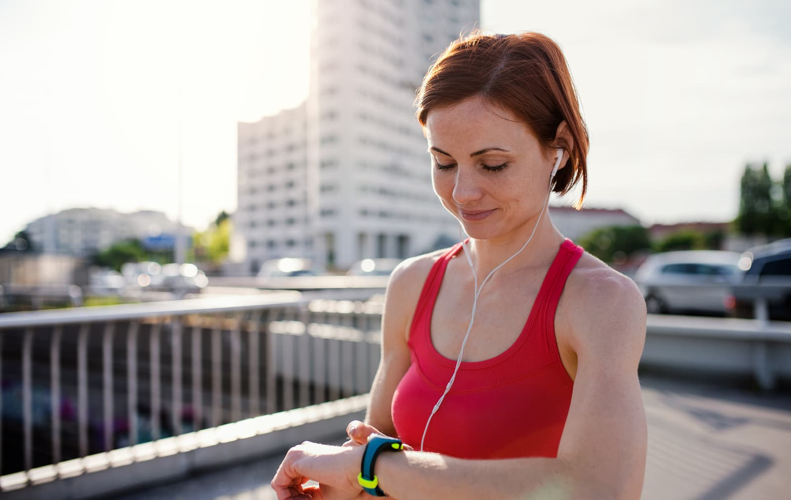 Young woman runner with earphones in city, using smartwatch.