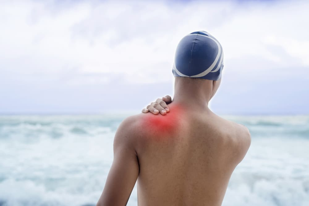 Swimmer holding sore shoulder before getting into the water