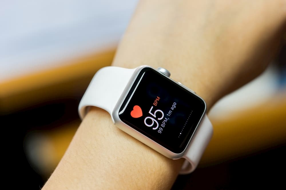 Close up of a white smart watch with health app icon on the screen