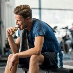 Man eating energy bar at gym after a workout