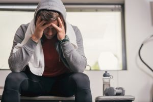 Man sitting on gym bench suffering depression.