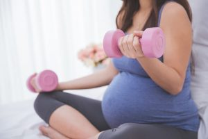 Pregnant woman doing exercise on her bed using dumbbell